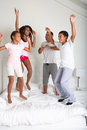 Family jumping on bed together having fun Royalty Free Stock Photo