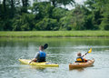 Family kayaking father and son on a lake or river with green grass and trees behind them man and boy are in nature rowing their Royalty Free Stock Photo