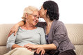 Family kiss loving adult daughter giving old mom a portrait of pretty women kissing and embracing her senior mother isolated on Royalty Free Stock Photo