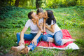 Family kiss sitting in the park summer morning Royalty Free Stock Photography