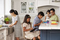 Family In Kitchen Doing Chores And Using Digital Devices Royalty Free Stock Photo