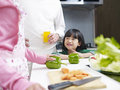 Family in kitchen little asian girl talking to parents and smiling Stock Photos