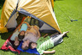Family laying in tent on lawn Royalty Free Stock Photo
