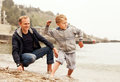 Family leisure at the sea father with son throw pebbles into Stock Image