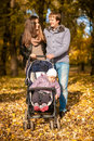 Family with little daughter in pram at autumn full length portrait of happy park Royalty Free Stock Photography
