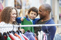 Family Looking At Clothes On Rail In Shopping Mall Royalty Free Stock Photo