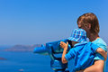 Family looking at the sea with binoculars in thira santorini greece Royalty Free Stock Photography
