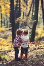 Family love and trust. Little boy kiss small girl friend in autumn forest. Brother kiss sister with love in woods Royalty Free Stock Photo