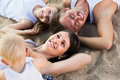 Family lying on beach, top view