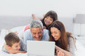 Family lying on bed using their laptop at home Stock Photo