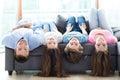 Family lying upside down on sofa Royalty Free Stock Photo