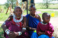Maasai family at threshold of his house, father and children.