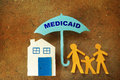 Family medicaid umbrella paper cutout with house under a Royalty Free Stock Images