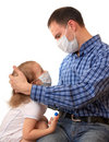 Family in medical masks with a thermometer. Royalty Free Stock Image