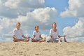 Family meditate over blue cloudy happy summer sky Royalty Free Stock Images