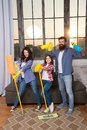 Family mom dad and daughter with cleaning supplies at living room. We love cleanliness and tidiness. Cleaning together
