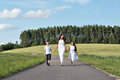 Family mom and two children girl and boy walking on the road in the park among the wheat fields and forests Royalty Free Stock Photo