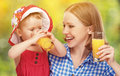 Family mother and baby daughter drinking orange juice in the sum summer outdoors Royalty Free Stock Photos