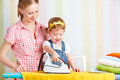 Family mother and baby daughter together engaged in housework ir happy iron clothes iron Royalty Free Stock Photo
