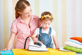Family mother and baby daughter together engaged in housework ir happy iron clothes iron Royalty Free Stock Photography