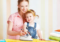 Family mother and baby daughter together engaged in housework ir happy iron clothes iron Stock Image