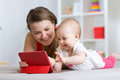 Family - mother and baby with tablet on floor at home. Woman and child girl relaxing at tablet computer.