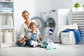 Family mother and child girl  in laundry room near washing machi Royalty Free Stock Photo