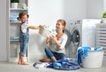 Family mother and child little helper in laundry room near washi Royalty Free Stock Photo