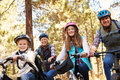Family mountain biking in a forest, looking to camera Royalty Free Stock Photo
