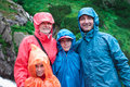 Family on mountain trail on a rainy day green slope in background Royalty Free Stock Images