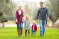 Family mum dad and kids walking outdoors in park Stock Photos