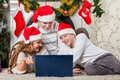 Family with notebook near christmas tree happy sitting at home Royalty Free Stock Image