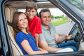 Family with one kid is travelling by car smiling and looking at camera Royalty Free Stock Image
