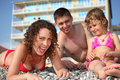 Family on pebble in swimwear Stock Photo