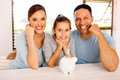 Family with piggybank cheerful of three at home Stock Photos