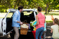 Family placing picnic items in car trunk Royalty Free Stock Photo