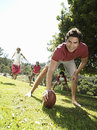 Family playing american football in park focus on man in foreground surface level tilt men Stock Images