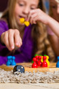 Family playing board game at home two sisters ludo on the floor focus on dice in the front Stock Photography