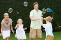 Family playing with bubbles in garden smiling Royalty Free Stock Image
