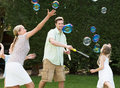 Family playing with bubbles in garden smiling Stock Photo
