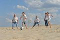 Family playing football on a beach in summer day Stock Photography