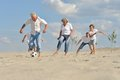 Family playing football on a beach in summer day Royalty Free Stock Image