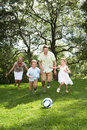 Family playing football in garden smiling Stock Photography