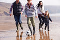 Family playing football on winter beach Stock Images