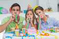 Family playing with party horns during a birthday Royalty Free Stock Photo