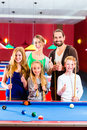 Family playing pool billiard game together with queue and balls on table Royalty Free Stock Photography