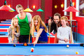 Family playing pool billiard game together with queue and balls on table Stock Photo