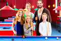 Family playing pool billiard game together with queue and balls on table Stock Images