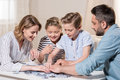 Family playing with puzzle on table at home together Royalty Free Stock Photo