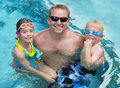 Family playing in the swimming pool a father with his two kids while on vacation Stock Photography
